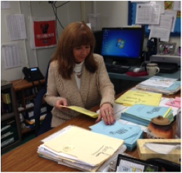 NHS adviser Shirlee Shoben prepares papers to hand out for the induction ceremony. Photo by Allison Ng.