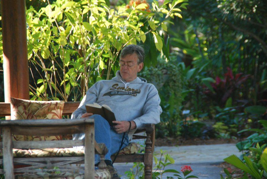 A man rests with his dog while reading a book at the Naples Botanical Gardens in Naples, Fla.
