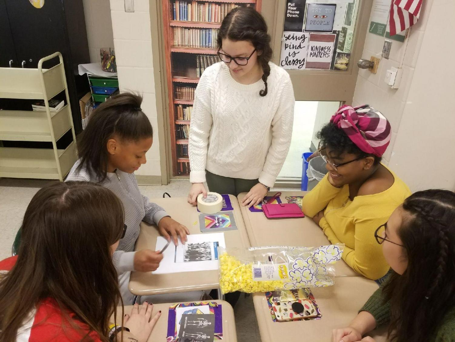 Mollie Davis leads a group of students in a small project at the most recent Women's Studies Club showing the important role of positive media.