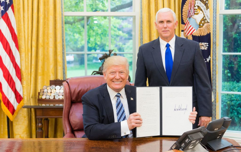 President Trump, joined by Vice President Mike Pence, displays a signed executive action order.