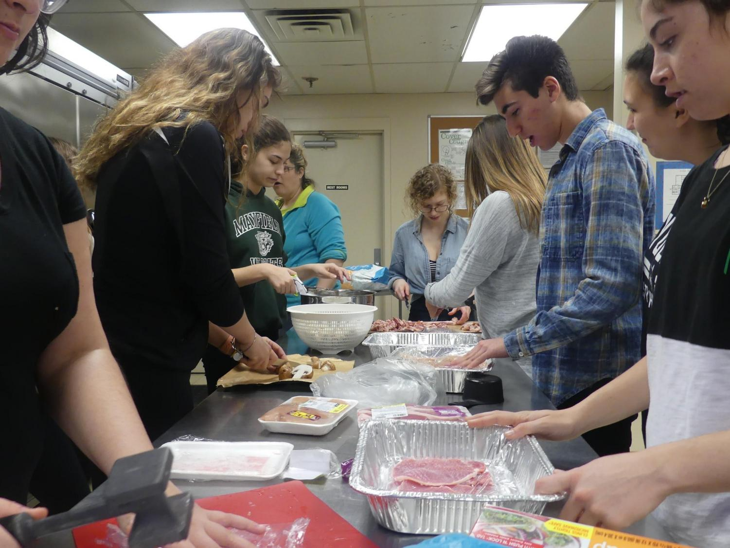 The club members make chicken cutlets at the annual dinner.