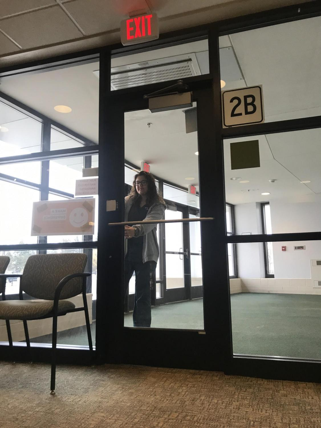 Junior Brianna Melarango waits in the vestibule to be buzzed into the school by a building secretary.  There is talk to possibly move the vestibule outside of the school to improve school safety.