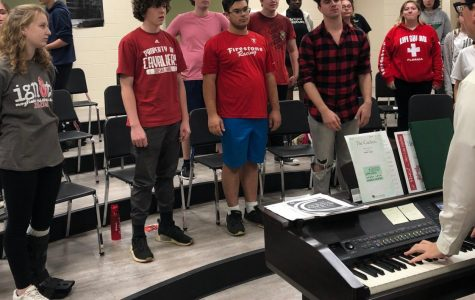 Brian Fancher, bottom right, plays the piano and helps his students warm up for rehearsal.  The Limited Edition show choir performs for the first time on Oct. 16.