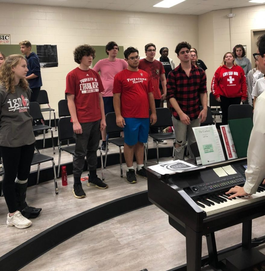 Brian+Fancher%2C+bottom+right%2C+plays+the+piano+and+helps+his+students+warm+up+for+rehearsal.++The+Limited+Edition+show+choir+performs+for+the+first+time+on+Oct.+16.