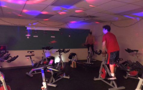 Instructor Abigail Ferritto engages the class with bright lights and intense music. Ferritto is on the left and Cody Piunno is on the right