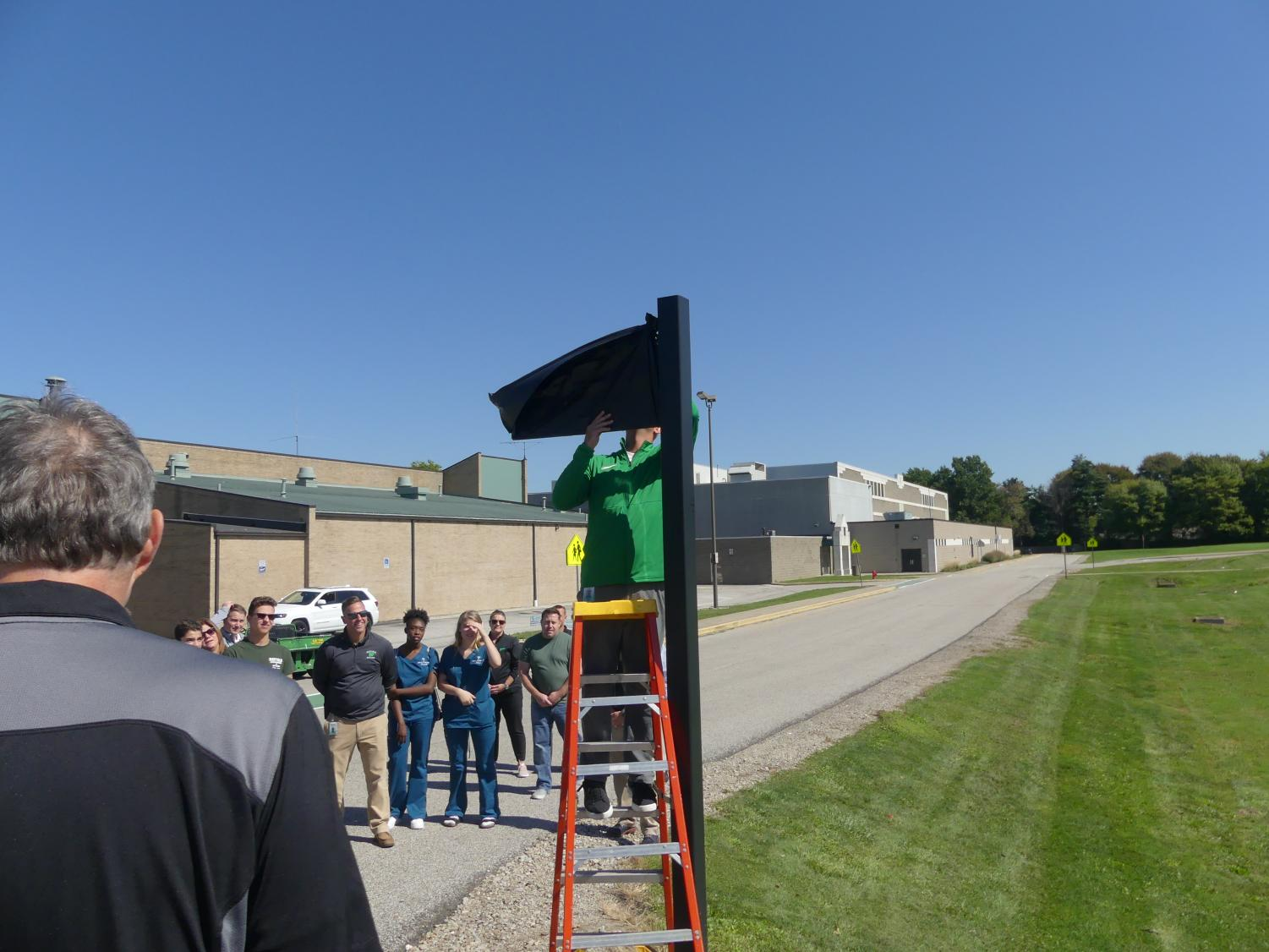Athletic director Keith Leffler removes the cover from the new Stevie street sign behind the school.  Assistant principal Brian Linn, the swim team, and other members of the community were there for the reveal as well.