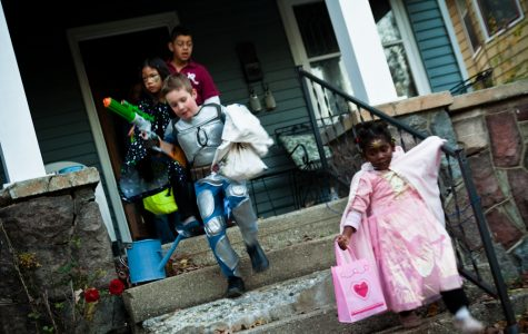 kids run off of a porch after collecting their candy on Halloween