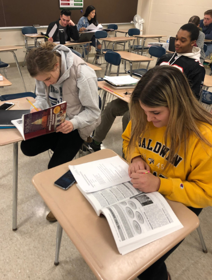 Seniors Breanna Veverka (left) and Gabby Tartaglia (right) use their government review books to prepare for the AIR test in Kris Kornblut's class.