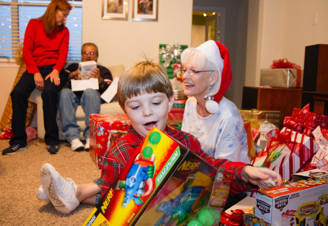 A+family+celebrates+Christmas+with+the+tradition+of+opening+presents+together.+
