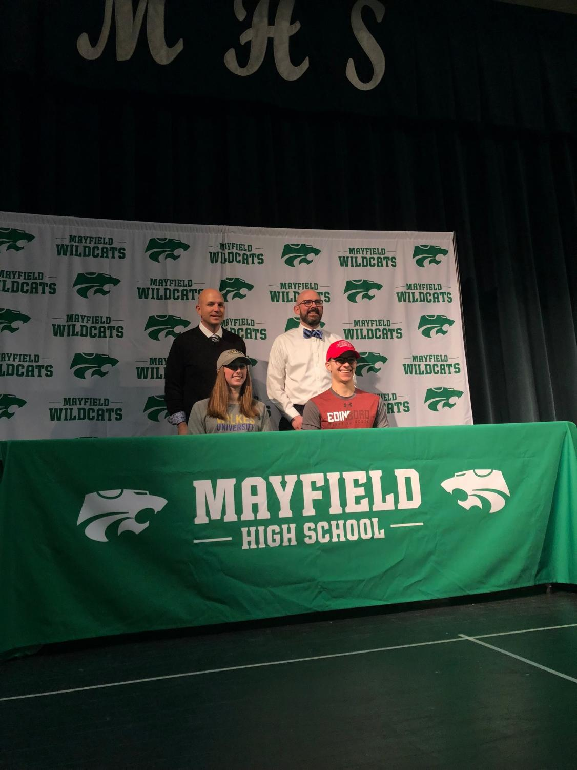 Keith Leffler and Jeffrey Legan stand behind senior signees during signing day.