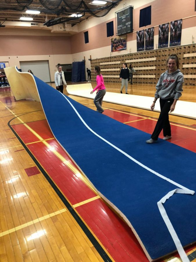 Gymnasts Lauren Lubin and Tori Soria set up the mats for practice at West Geauga High School.