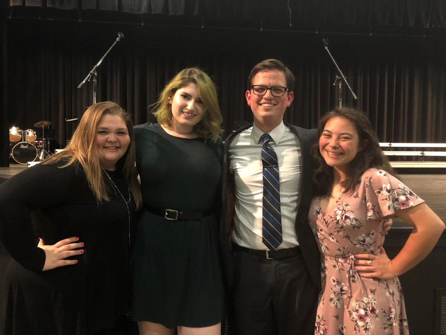 Seniors Katelyn Korver, Shea Page, and Liz Corpus enjoy a final moment with choir director Brian Fancher after the show.