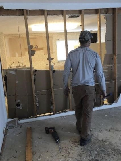 Ferritto's father-in law helps tear down the walls in the new house in preparation for renovation.