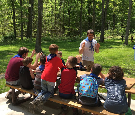 Matthew Szigeti (standing in white) singing with the Cub Scouts at a scout outing on Saturday May 11, 2019.