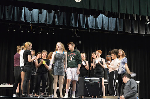 "The cast rehearses the song ""They Both Reached for the Gun"" in partial costume.  Morgan Beck, center, is excited about the performances that start on Thursday.  She said, ""Expect a fun show full of crazy twists and turns. The world of Chicago is full of murder, adultery, love, and loss therefore who wouldn't want to come see it?"""