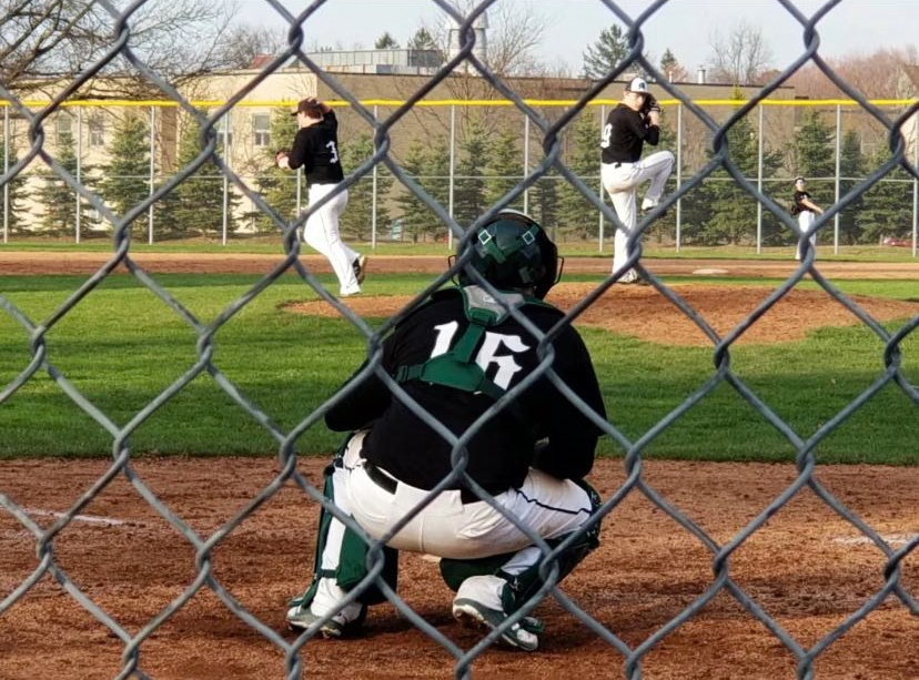 BRING THE HEAT! Sophomore catcher Dylan Gamber takes warmup tosses in a game last season.  Gamber is hoping to earn a spot on this years varsity roster.