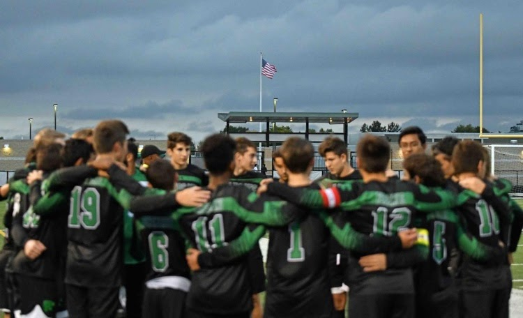"""The Varsity Soccer Team circles up before a home game. """"It really feels like a family,"""" said junior Nico Marella, next year's captain."""