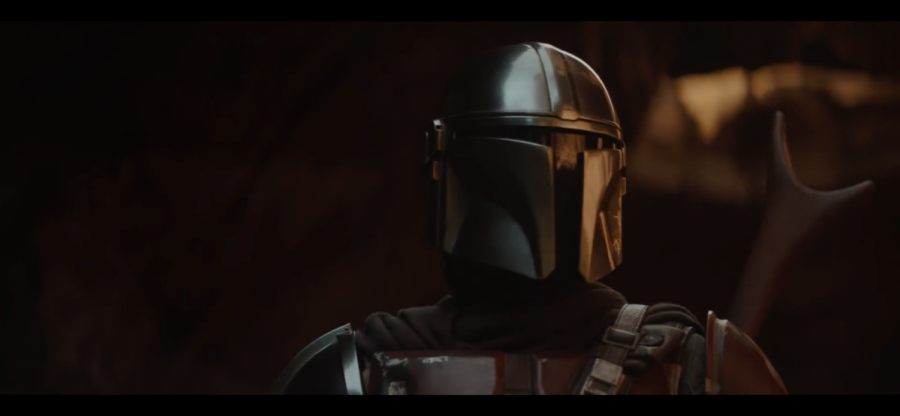 The Mandalorian, played by actor Pedro Pascal, checks his surroundings for danger.