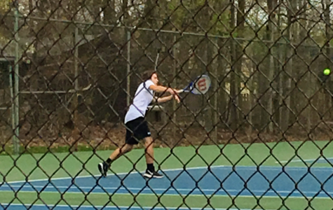 Senior Ben Kloppman volleys with his opponent during a match last season.