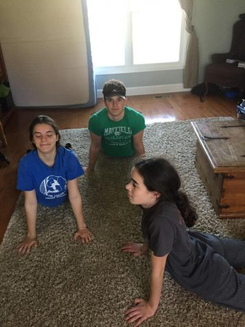 Senior Joe Isabella (center) does yoga with two of his sisters.