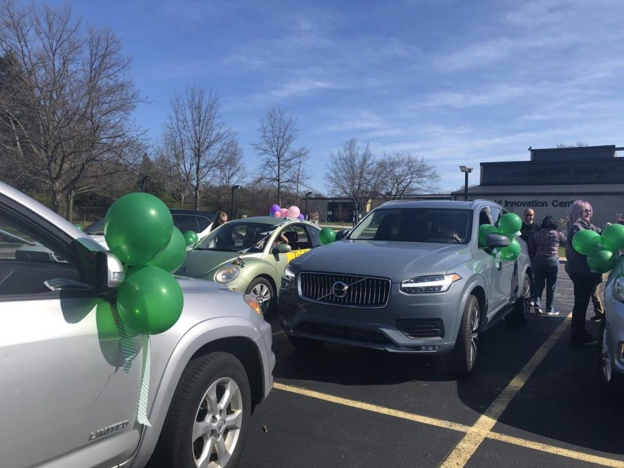 "Alexis Glumm, Larry Braun, Andi Cerrillo, and Danielle Varanese decorate cars in preparation for the parade. ""The day of, we all gathered at the Innovation Center parking lot beforehand to decorate our cars with balloons and streamers,"" said Darcy Horvat."