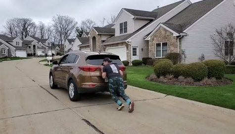 Sophomore Dylan Gamber has been creative with his strength training, as he pushes a car near his home.
