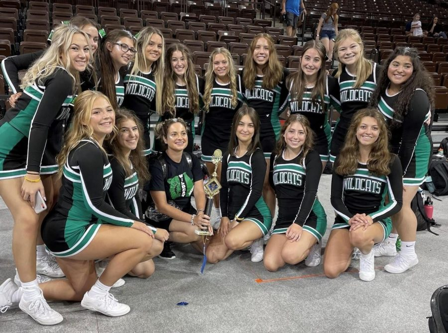 The varsity cheerleaders celebrate their cheer camp trophy with head coach Gabby Velotta.